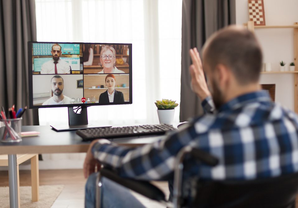 Invalid freelancer in wheelchair during a video call working from home. Young immobilized businessman doing his business online, using high technology, sitting in his apartment, working remotely in special conditions.